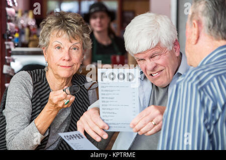 Man has difficulty reading menu in a cafe without reding glasses - Stock Photo