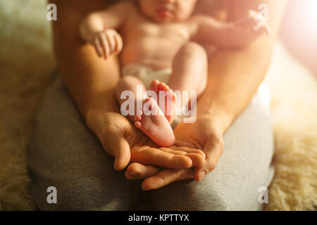 Mother holds newborn baby's feets. Tiny feet in woman's hand. - Stock Photo