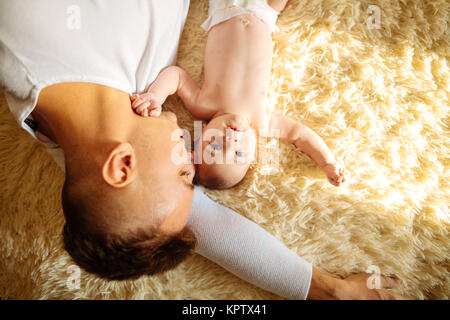 Father lying on bed and holds his baby - Stock Photo