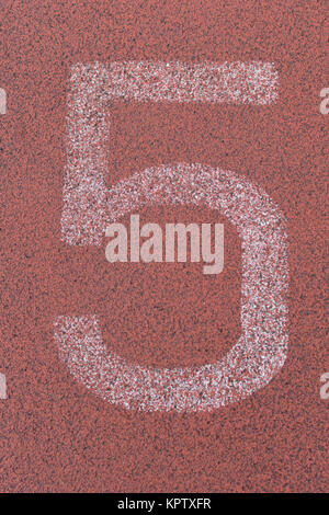 Large white track number on red running track, series of 1 to 7. - Stock Photo