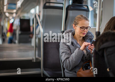 Pretty, young woman on a streetcar/tramway, during her commute to work. Using her smartphone. (color toned image - Stock Photo