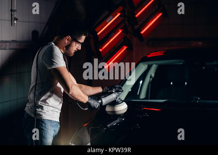 Car detailing - man with orbital polisher in auto repair shop. Selective focus. - Stock Photo
