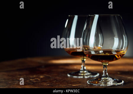 Close up of two glass goblets with alcohol resting on a wooden table against a dark background - Stock Photo