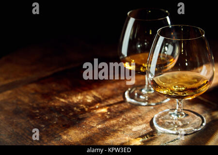 Close up of two bourbon filled glasses on wooden table in a dark room with a few rays of sunlight - Stock Photo