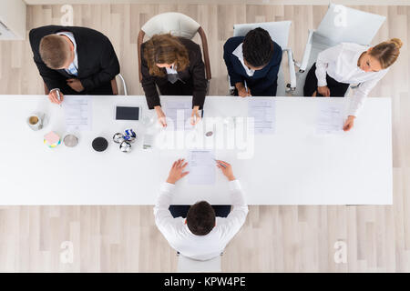 Businesspeople Interviewing Young Male Applicant - Stock Photo