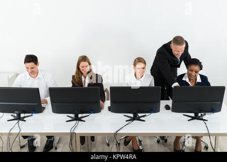 Businessman Helping His Colleagues In The Office - Stock Photo