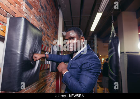 person wearing business suit and boxing gloves. - Stock Photo