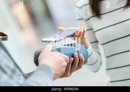 Customer pay with mobile phone - Stock Photo