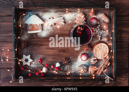 Mulled wine or punch in glass, christmas cookies, dry oranges and lights on dark rustic vintage background, top - Stock Photo