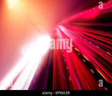 Artistic dynamic image of colorful light trails of busy highway traffic on a foggy night, Highway 401, Toronto, - Stock Photo
