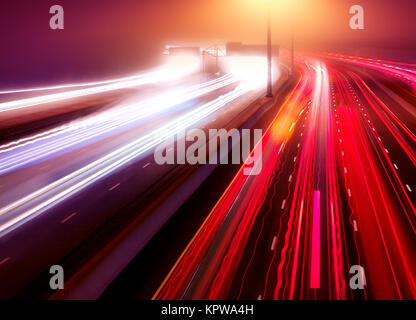 Artistic abstract traffic light trails. Busy highway traffic on a misty night, Highway 401, Toronto, Ontario, Canada. - Stock Photo