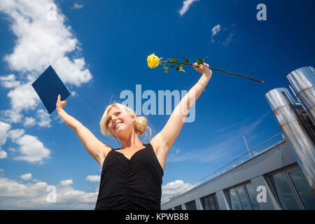 Pretty, young woman celebrating joyfully her graduation - spreading wide her arms, holding her diploma, savouring - Stock Photo