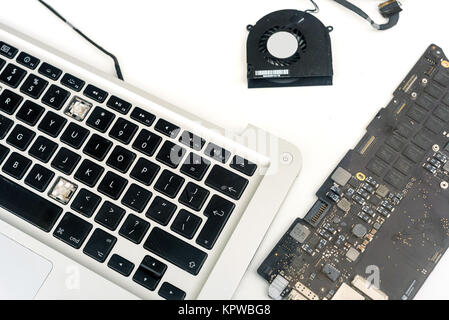 Broken components of an apple macbook ipad computer on a white background with a copyspace area for computer repair - Stock Photo