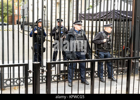 Armed police officers outside the gates of 10 Downing Street in London providing protection against the famous London - Stock Photo