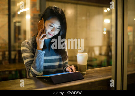 Woman talk to cellphone and use of tablet at coffee cup - Stock Photo
