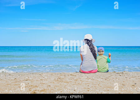 Brunette with long hair and kid turned away - Stock Photo
