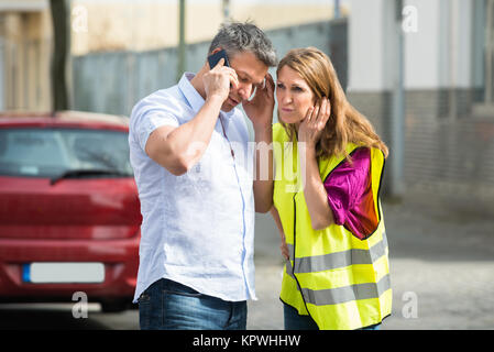Couple Using Mobile Phone With Broken Down Car - Stock Photo