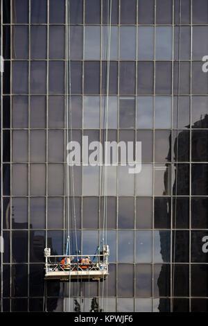 Fensterputzer stehen in einem Aufzug und putzen die Fenster eines Hochhauses. - Stock Photo