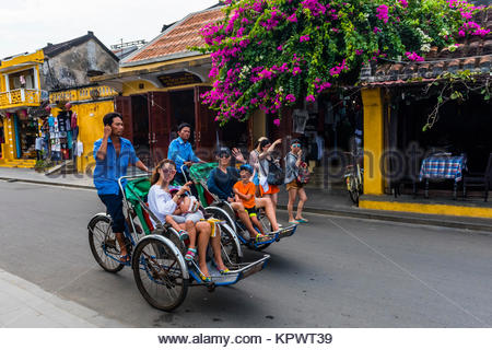 Tourists peddled through the Old Town on Cyclos (three wheeled bicycle taxis), Hoi An, Vietnam. - Stock Photo