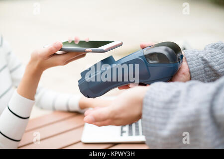 Woman using mobile phone to pay - Stock Photo