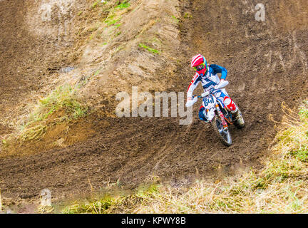 Extreme sport. A rider on a motorcycle rides the sand. Racer on motocicle in blue clothes - Stock Photo