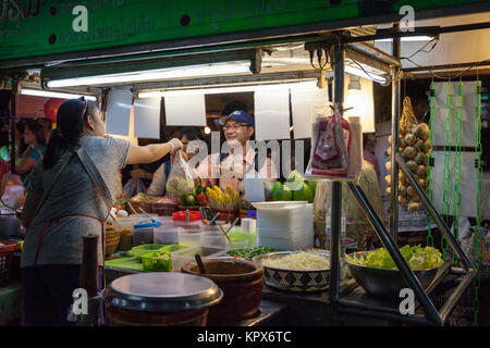 CHIANG MAI, THAILAND - AUGUST 27: Woman sells traditional Thai food at the Saturday Night Market (Walking Street) - Stock Photo