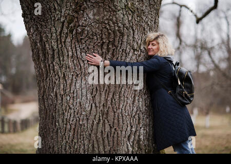 Beautiful blonde girl is hugging tree trunk - Stock Photo