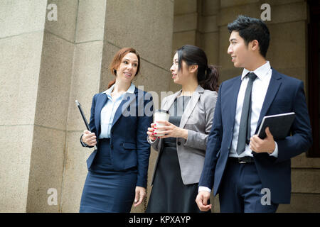 Group of business people walking out of office - Stock Photo
