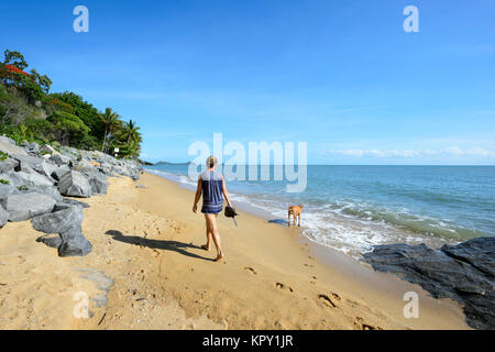 Woman walking her dog on Trinity Beach, a popular Northern Beaches suburb of Cairns, Far North Queensland, FNQ, - Stock Photo