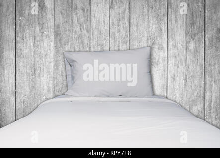 Close up white bedding and pillow on wooden background - Stock Photo