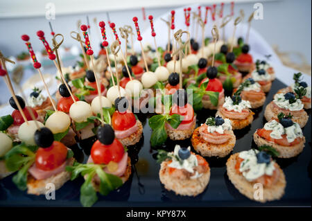 Served festive candy bar table with cupcakes tower and love is sweet sign - Stock Photo