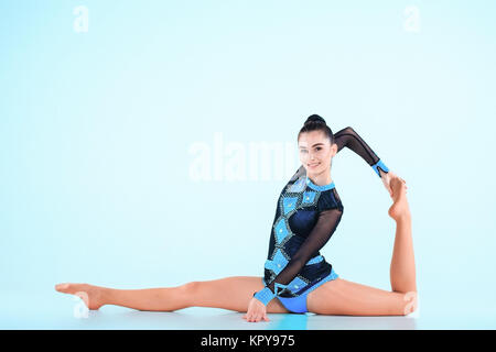 The girl doing gymnastics dance on a blue background - Stock Photo