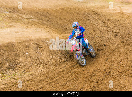 The racer on a motorcycle participates in race motocrosses, goes on sand. Blue suit. Close-up. Stock Photo