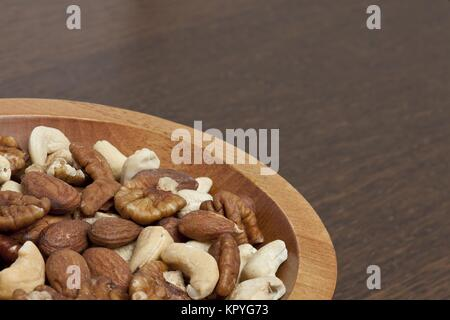 mixed nuts on a wooden bowl - Stock Photo