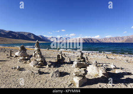 Young caucasian boy playing at stone towers by the Pangong Tso lake in windy conditions, Ladakh, Jammu and Kashmir, - Stock Photo