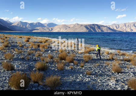 Woman and young boy, 7, walking trough dry beach covered with yellow grass on high altitude by the lake Pangong - Stock Photo
