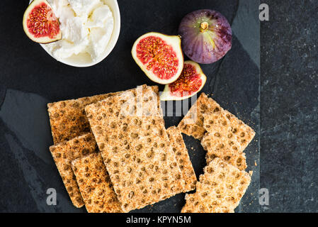 Wholegrain rye crispbread crackers, figs and ricotta cheese are ready for the healthy snack, dark background - Stock Photo