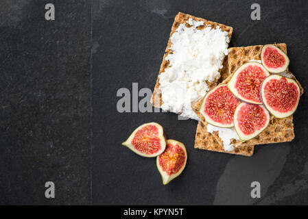Healthy snack from wholegrain rye crispbread crackers, figs and ricotta cheese on dark slate board - Stock Photo