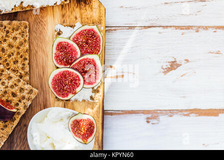 Healthy snack from wholegrain rye crispbread crackers, figs and ricotta cheese on light wooden background - Stock Photo