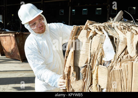 Worker in Hazmat Suit Sorting Cardboard at Recycling Factory - Stock Photo