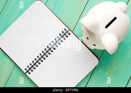 Piggy bank and open notebook. - Stock Photo