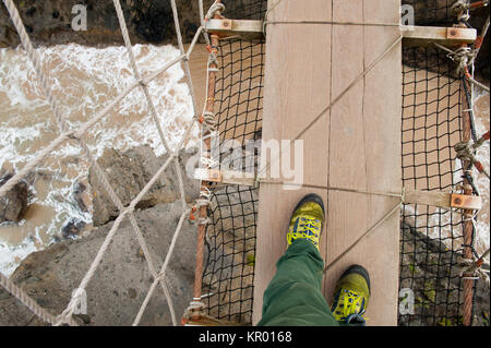 Legs and hiking shoes of a man walking on the famous tourist attraction Carrick-a-Rede Rope Bridge, Ballycastle, - Stock Photo
