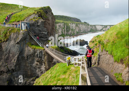 Ballycastle, Northern Ireland, UK - September 2017: People crossing the Carrick-a-Rede Rope Bridge, a famous tourist - Stock Photo