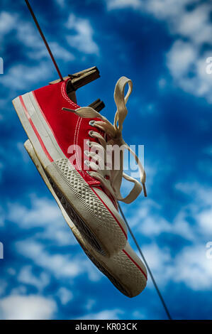 pair of red sneakers on clothesline - Stock Photo