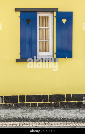 Blue window with hearts and yellow wall - Stock Photo