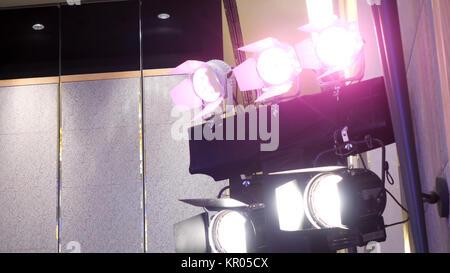 Theater spot light with smoke against wall. Spotlight, illuminator, lamp - Stock Photo