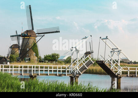 beautiful traditional dutch windmills near the water channels with drawbridge - Stock Photo