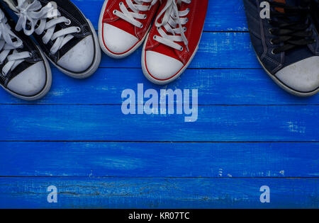 Three pairs of sneakers of different sizes - Stock Photo