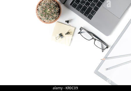 Desk with laptop, eye glasses, notebook and small cactus isolated on white background. Top view with copy space. - Stock Photo