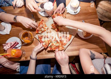 Friends eating pizza at home party, closeup - Stock Photo